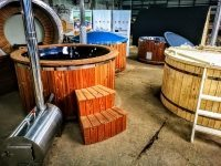 Outdoor whirlpool jacuzzi with thermo wood decoration and external wood burner